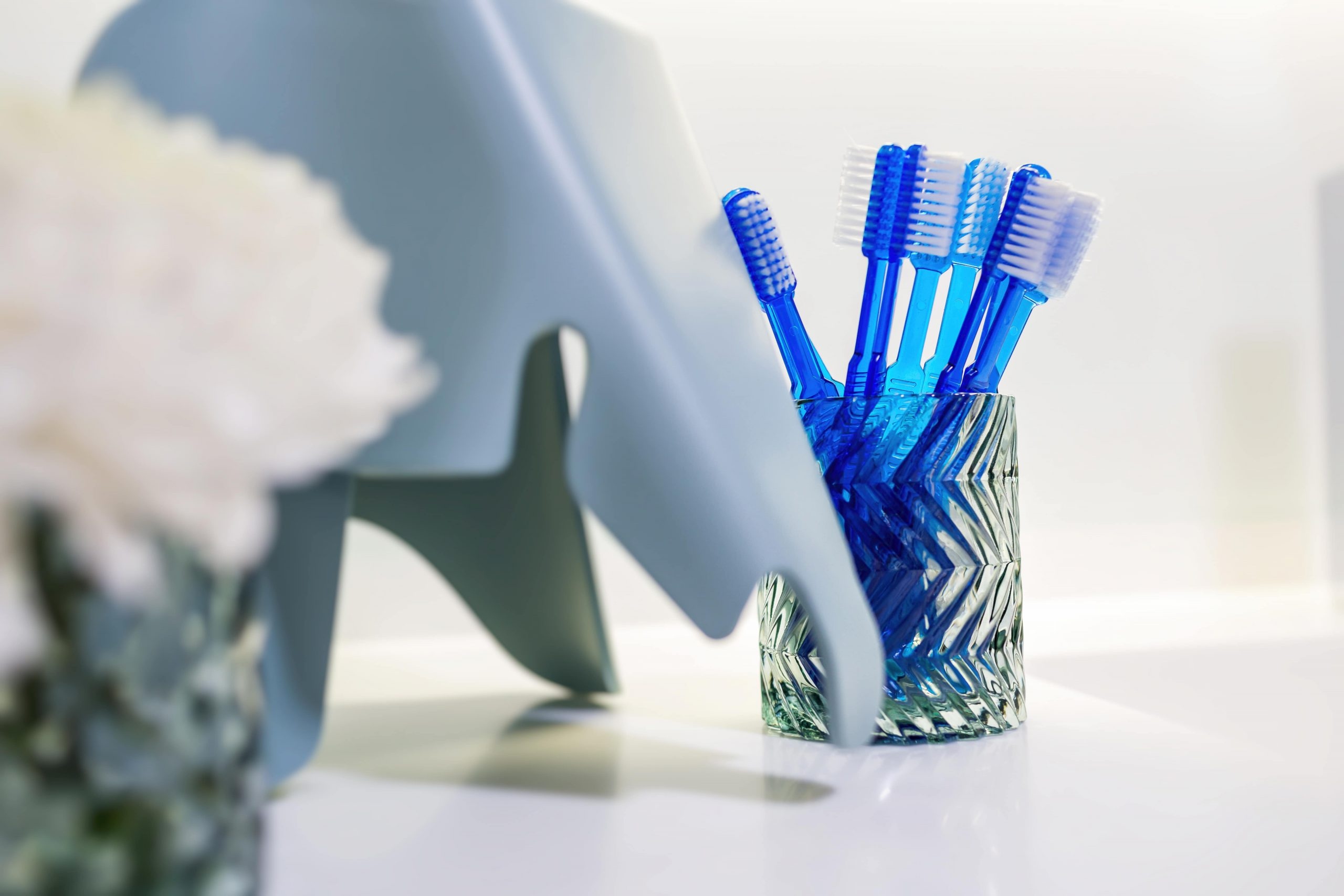 Prophylaxe und Mundhygiene spielerisch mit blauen Zahnbürsten und Elefanten.